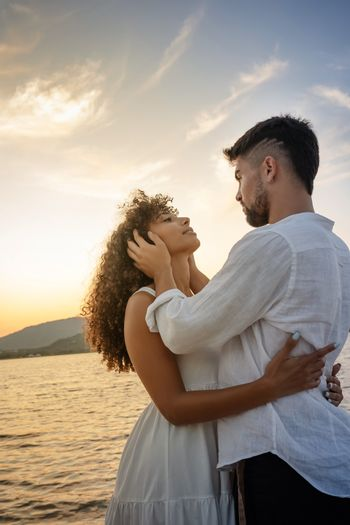 Young attractive caucasian bearded man with modern haircut holds his black Hispanic girlfriend's head in his hands looking into her eyes while she hugs him - Multiracial couple romance scene at sunset