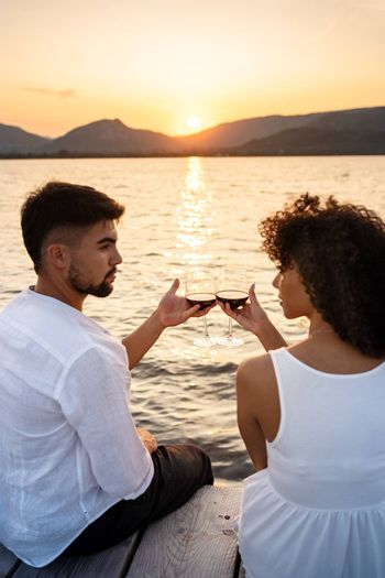 Romance scene of multiracial couple sitting on a pier at sunset or dawn toasting with red wine looking each other in the eyes - Attractive man bonding with her Hispanic girlfriend - Focus on glasses
