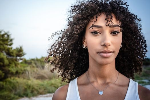 Femininity and beauty in nature: close up portrait of beautiful black Hispanic young woman with curly dark long hair looking confident at the camera - Make-up female artist with perfect mouth and eyes
