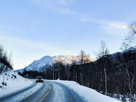 Driving through snowy road and landscape, Norway. Car in front.