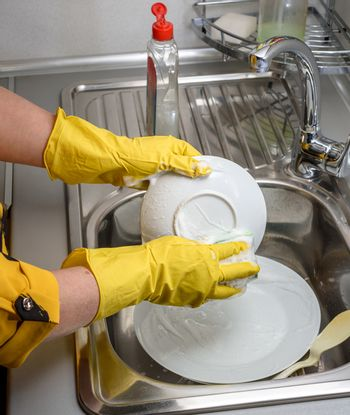 A woman in gloves washes dishes, only her hands