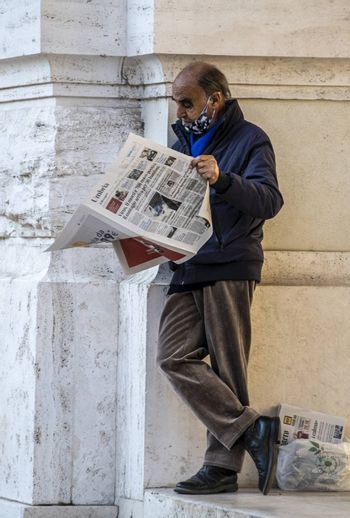 terni,italy november 06 2020:man leaning against a building reading the newspaper