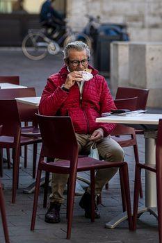 terni,italy november 06 2020:man sitting at a table eats a piece of pizza
