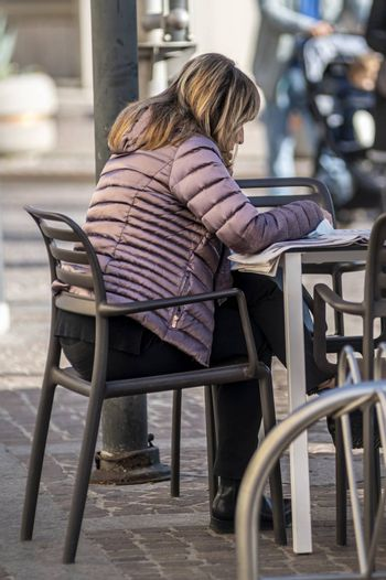 terni,italy november 06 2020:woman sitting at a table in a cafe reads the newspaper