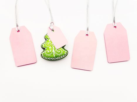 Four pink clear tags and decorative Chrsitmas tree on white background. Glamorous labels on silver threads with copy space. New Year symbol of sale and shopping. Top view, flat lay.