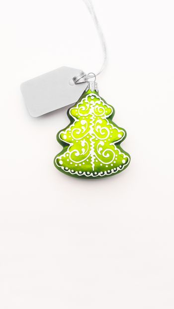 Decorative Christmas tree  with grey price tag on white background. Clear label on silver thread. New Year symbol of sale and shopping. Top view, flat lay.
