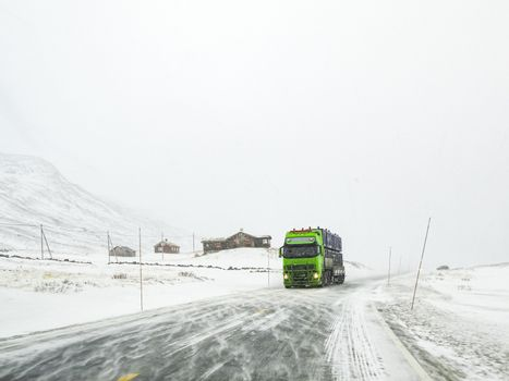 Driving through snowy road landscape, Norway. Green truck in front.
