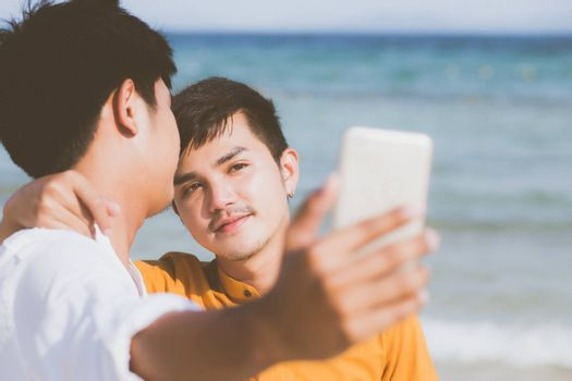 Gay portrait young couple smiling taking a selfie photo together with smart mobile phone at beach, LGBT homosexual lover in the vacation at sea, two man going to travel, holiday concept.