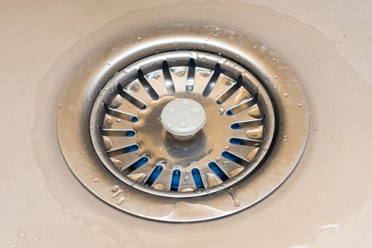 Drain in the sink with a mesh lid close-up