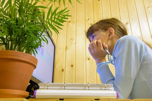 A student sits in front of the computer during distance learning and looks thoughtfully at the screen