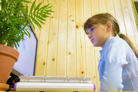 The student sits at the table in front of the monitor and carefully reads the task