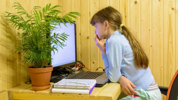 A schoolgirl thoughtfully reads a problem in an online lesson with distance learning
