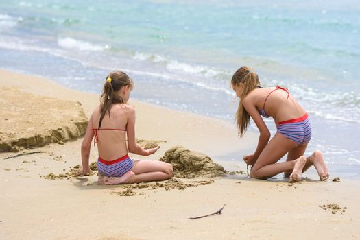 Two girls build sand castles on the seashore, back view