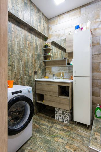 Interior of a cozy compact modern bathroom with a washing machine