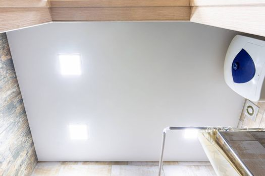 Stretch matte ceiling in the bathroom with three square lamps