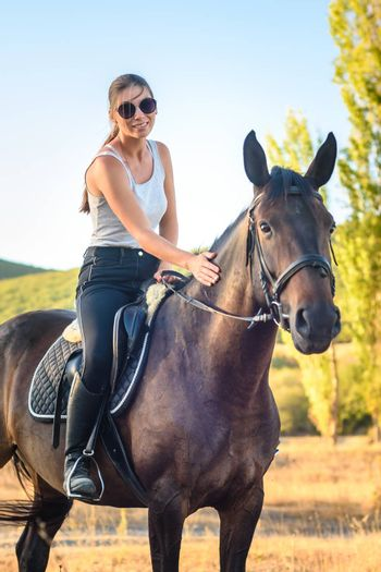 Beautiful slender pretty girl sitting on a horse, close-up
