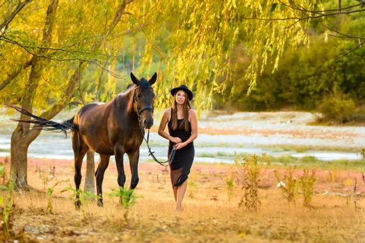 A girl in a beautiful black dress and a black hat walks with a horse across the field