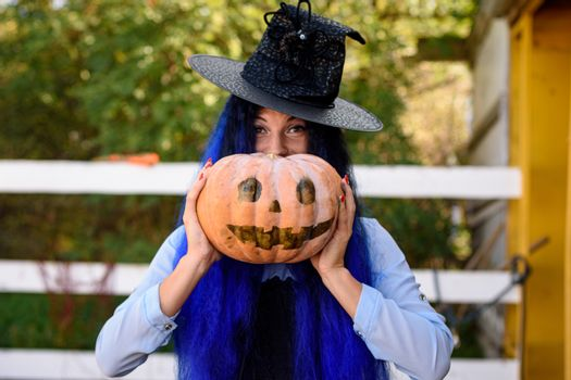 A girl in a witch costume looks out from behind a pumpkin with a painted face