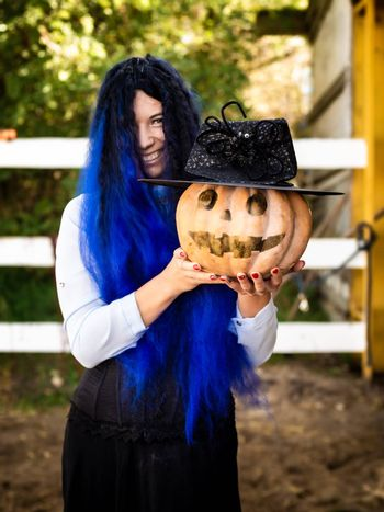 A girl dressed as a witch with blue hair is holding a pumpkin with a painted face and a witch's cap