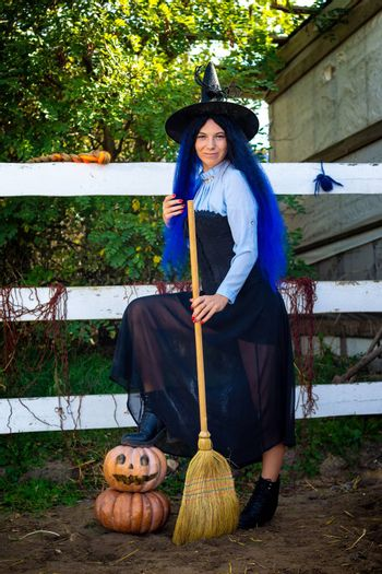 Cute girl in a witch costume with pumpkins and a broom at a Halloween party