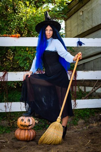 Cute girl in a witch costume with pumpkins and a broom