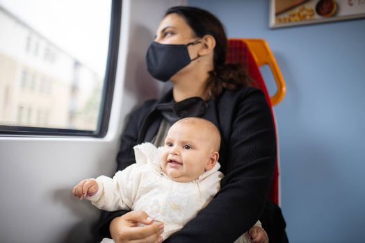 Woman wearing a face mask and black clothes, looking through the window of a bus as she holds her smiling baby