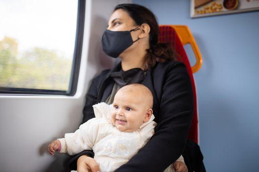 Woman wearing a face mask and black clothes and looking through the window of a bus as she holds her smiling baby