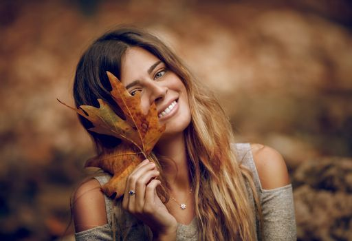 Portrait of a Beautiful Girl Having Fun in Autumn Forest. Holding in Hand Dry Maple Leaf. Beauty of Fall Season.