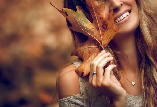 Closeup Portrait of a Pretty Woman Covering her Face with Dry Maple Leaf. Face Part. Happy Autumn Holidays. Beauty of Fall Nature.