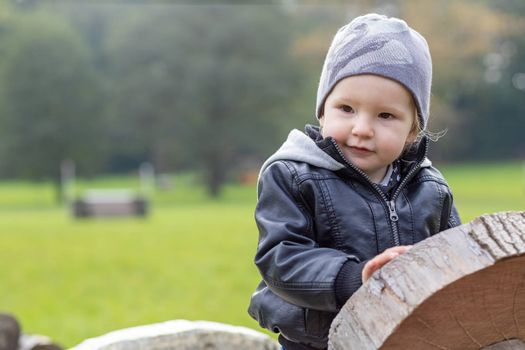 Cute little boy dressed in a leather jacket is sitting on wooden toy in autumn park