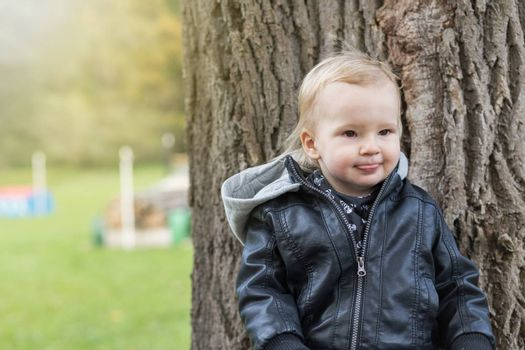 Adorable little boy dressed  in a leather jacket is sticking out his tongue outdoors.