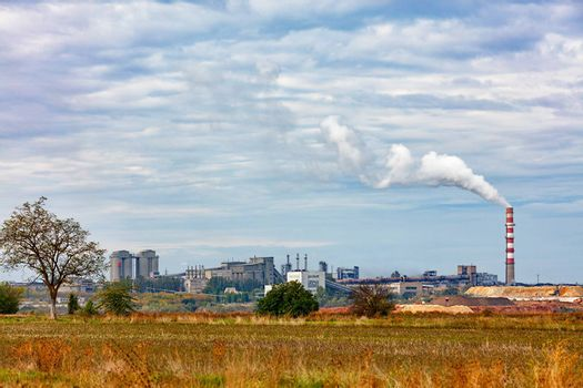 Cement plant on the horizon with a smoking chimney and a quarry amid agricultural field and blue cloudy sky, copy space.