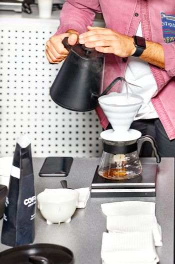 The barista's hands are preparing coffee by pouring boiling water into a white funnel.