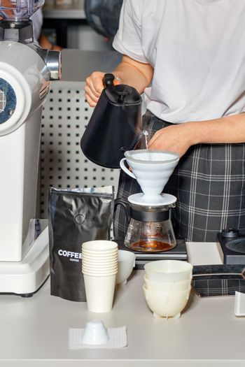 The barista's hands are preparing coffee by pouring boiling water into a white dripper.