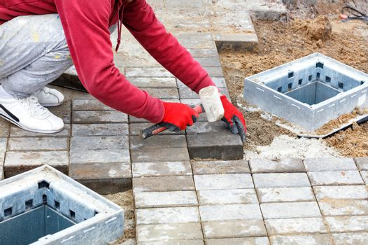A worker lays paving slabs on the sidewalk around the utility shafts.