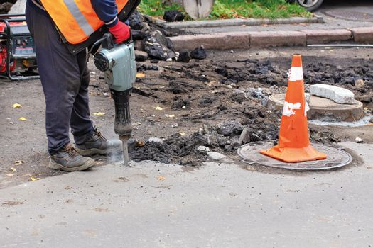 A worker uses an electric jackhammer to tear old asphalt off the road.
