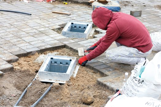 A worker installs utility shafts and lays paving slabs around them.