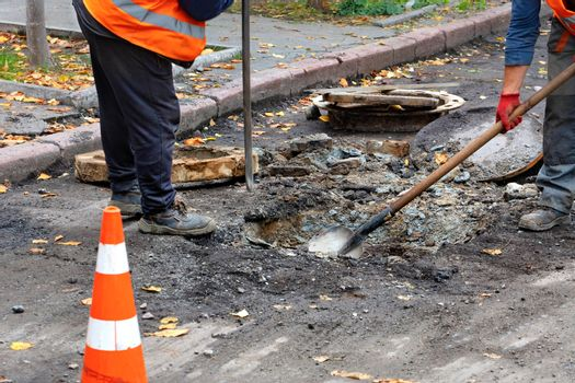 A team of road workers dig out an old sewer hatch with a crowbar and a shovel.