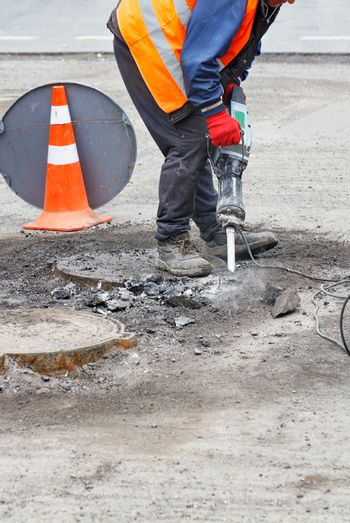 A worker repairs a section of the road with an electric jackhammer.
