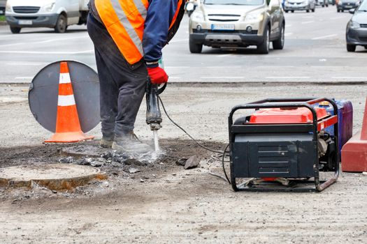 A worker repairs a section of the road with an electric jackhammer against the background of passing cars in blur.