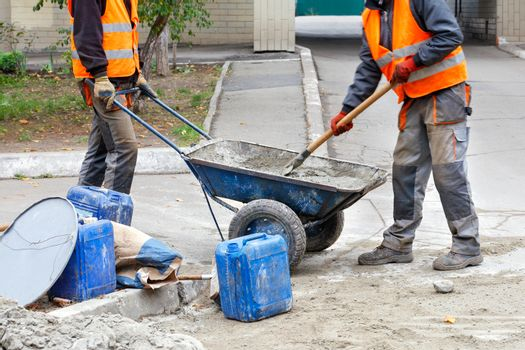 Workers in a trolley prepare concrete for repairing road curbs.