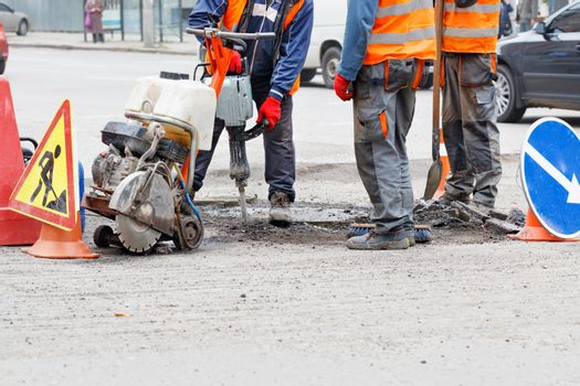 A team of road workers repairs a section of road with an electric jackhammer, petrol cutter, shovel and brush.