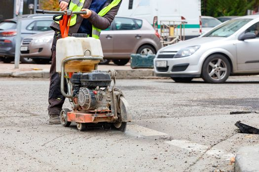 A worker cuts the old asphalt on the road with a gasoline cutter against the background of a city street and passing cars in blur.