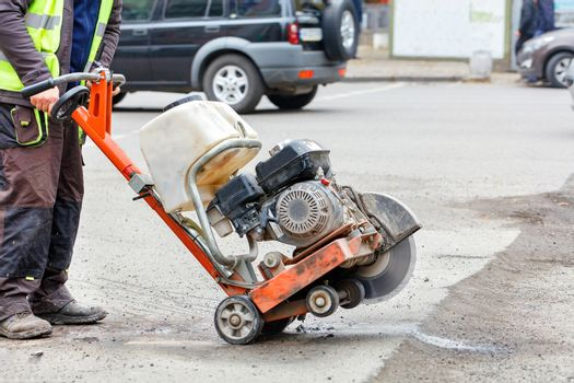 A worker moves a petrol cutter with a working diamond cut-off wheel to a bad section of the road that needs repair.