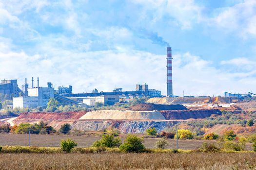 A production complex of a sand and clay quarry, a cement plant on the horizon in a blue haze.