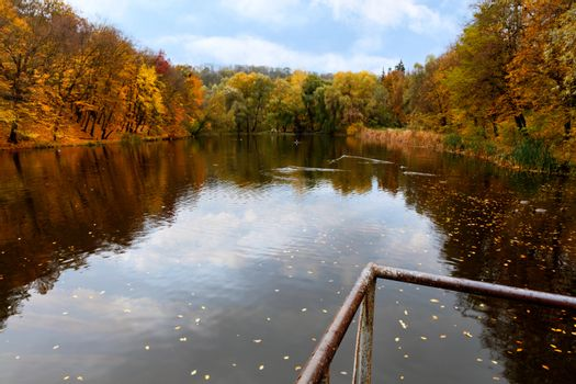 The metal railings of the old bridge indicate the landscape of an autumn forest lake in blur.