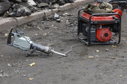 Electric jackhammer with a petrol generator at the workplace against the background of the road section being repaired.