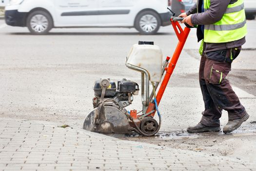 A worker cuts the old asphalt with a gas saw on the carriageway against the backdrop of a city street.