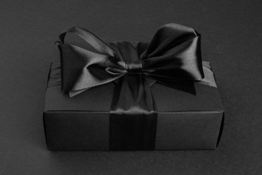 Black friday sale box gift present with ribbon bow on black conceptual design