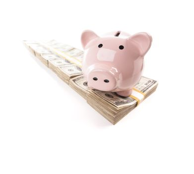Pink Piggy Bank on Row of Hundreds of Dollars Stacks Isolated on a White Background.